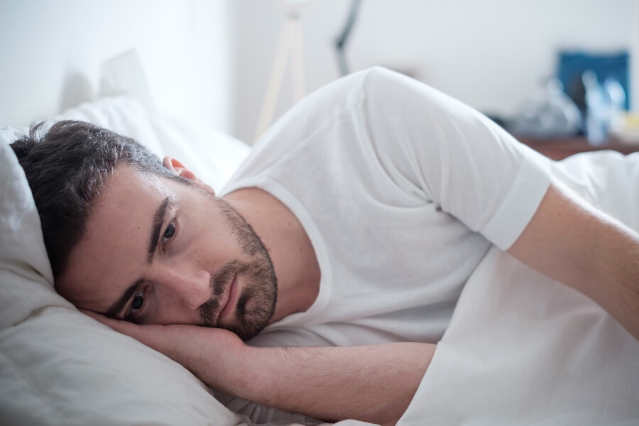 Mens mental health - showing a man in bed.